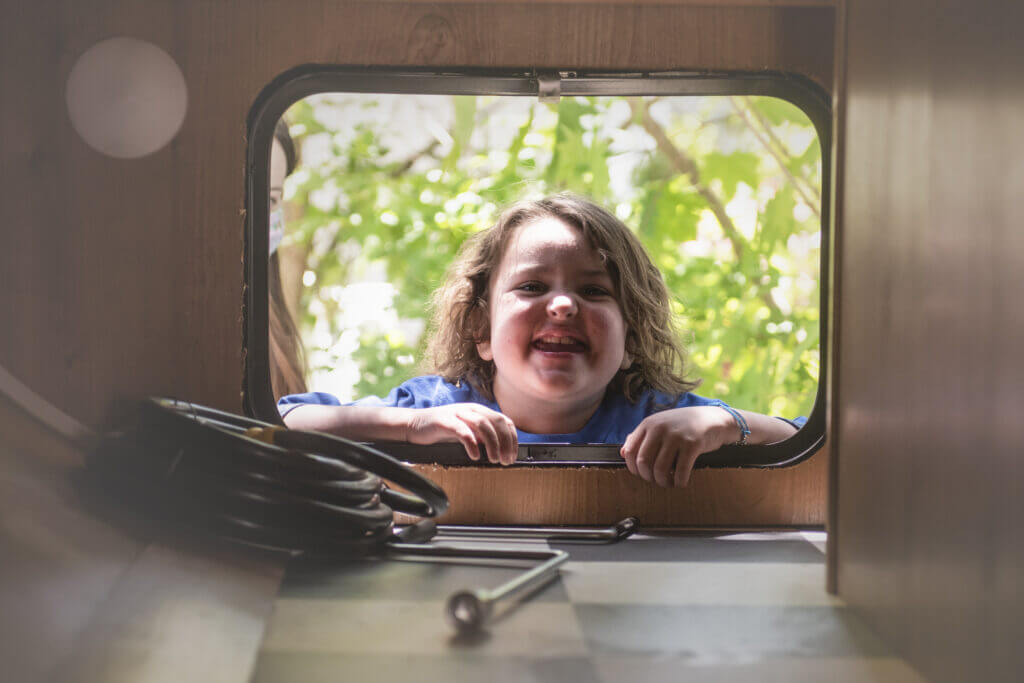 ellie smiles in the window of her bunkhouse travel trailer